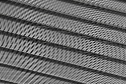 Background of wavy metallic grid with holes. Metal mesh as background. Perforated metal back.