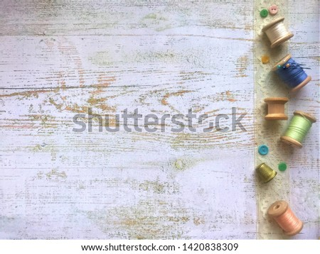 Background of white shabby wood with space for text, left on a lace ribbon ivory laid out vintage wooden reels with threads of pastel colors, reel empty, small multi-colored buttons, pins and thimble #1420838309