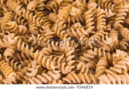 Background of whole wheat Fusilli pasta on white background