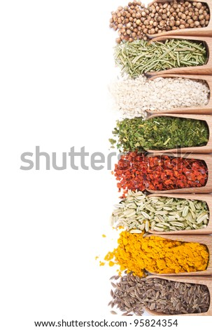 Background of wooden scoops with different spices scattered from them