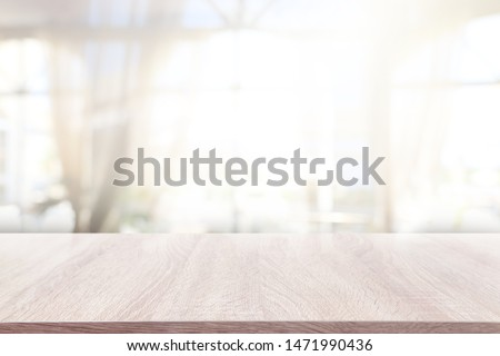 background of wooden table in front of abstract blurred window light Stockfoto ©