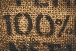 Background of woven textured hessian stamped with one hundred percent - 100 percent - in numerals