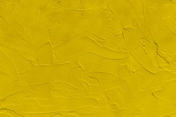 Background of yellow plastered wall close up. Mustard color backdrop.