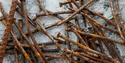 Background old rusty nails and rebar close-up in blurred selective focus on a light background