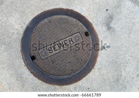 Background or texture: Cast iron sewer manhole lid flush with sidewalk - stock photo