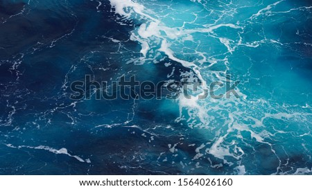 background pacific ocean, bright blue color of sea splashing wave, texture of sea foam. abstraction of ripped water waves in ocean sunlight. turbulent ocean composition. unusual structure of water.