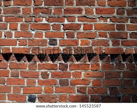background, part of the historic wall of the old red brick