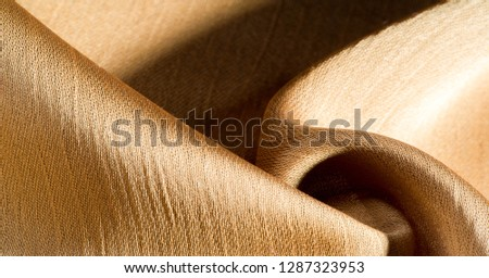 Background, pattern, texture, beige golden silk fabric It has a smooth matte finish and is durable due to a slightly twisted yarn. Use this luxurious fabric for anything - from design to your projects #1287323953
