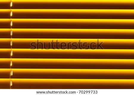 Background pattern texture of yellow plastic blind blocking out bright sunlight shining through window.