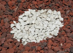 Background photo of piles of red pumice rocks with a circular pile of white limestone rocks