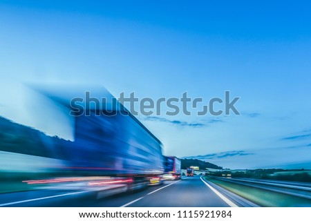 Background photograph of a highway in night. Trucks drive on a highway, motion blur and light trails. Evening or night shot of trucks, transportation, logistics on a highway or freeway.