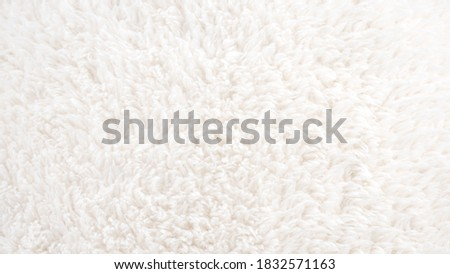 Background picture of a soft fur white carpet. wool sheep fleece closeup texture background. Fake color beige fur fabric. top view. Stock photo ©