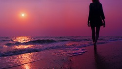 Background purple sunset on the sea. Silhouette of a girl walking along the sea