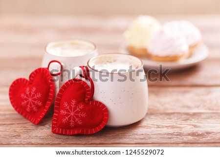 Background romantic mood. Two cups of coffee with decorative felt hearts for Valentine's Day or Birthday, Christmas. Wooden background. Cakes on blurred background. Selective focus, close-up #1245529072