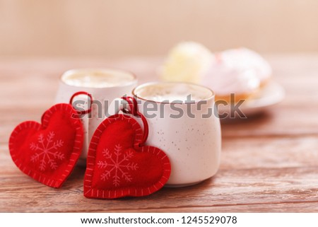 Background romantic mood. Two cups of coffee with decorative felt hearts for Valentine's Day or Christmas, wedding day. Wooden background. Cakes on blurred background. Selective focus, close-up #1245529078