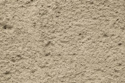 Background rough sand-colored wall. Old sand facade finish. Textured surface with shallow relief, many small dimples and bumps, old facade plaster