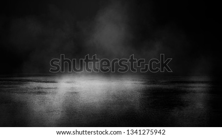 Background scene of empty street. Night view of the river, the night sky with clouds, the reflection of light on the water. Smoke fog