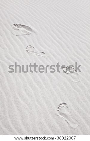 """Background shot of footprints in pristine, wind blown white beach sand. Good """"shifting sands of time"""" concept."""