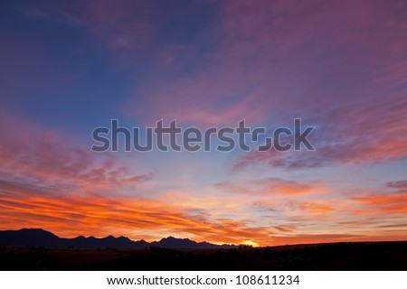 background sun filtered cloudscape morning sunrise over silhouetted mountains