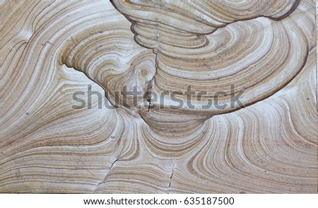 Background surface of decorative stone, sandstone with lines, volcanic material for cladding. The texture of a rocky plate with mystical patterns similar to waves, veins and clouds. #635187500