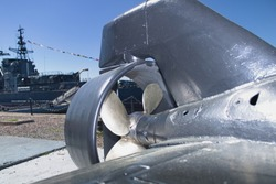 Background. Tail section of a miniature spy submarine mounted on a pier