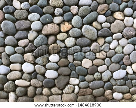 Background texture: mosaic of fine sea pebbles. Small pebbles lie exactly next to each other.