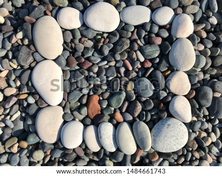 Background texture: mosaic of fine sea pebbles. Small pebbles lie exactly next to each other. Pebble frame on the seashore.