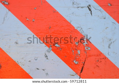 Background Texture of a Dirty and Scratched Orange and White Striped Stop Sign