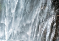 Background texture of a powerful torrent of white water cascading down a cliff in a mountain waterfall
