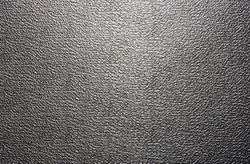 Background texture of a shiny metal sheet with a rough stippled textured surface reflecting light