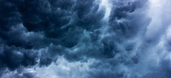 Background texture of dark storm clouds of the sky before a thunderstorm in rainy weather. Baner. Dramatic ominous dark blue clouds.