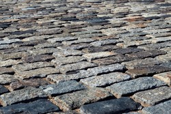 Background texture of rectangle tiles made of brown and gray old natural stone. Grey brick street paving of road, pavement in perspective view
