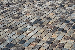 Background texture of rectangle tiles made of brown and gray old natural stone. Grey brick street paving of road, pavement