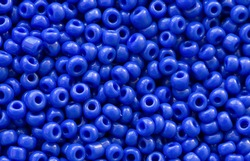 Background texture of Royal blue color beads closeup. Seamless beads texture. Hobbies, handmade jewelry, craft. Abstract background