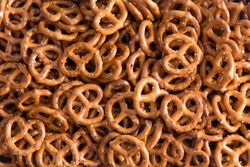 Background texture of salted savory mini pretzels in the traditional looped knot shape in a random heap viewed full frame from overhead