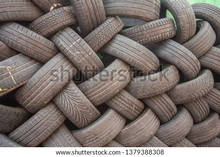Background, texture of the wall of tires laid at an angle. Black tire rubber, vehicle part, spare part. #1379388308