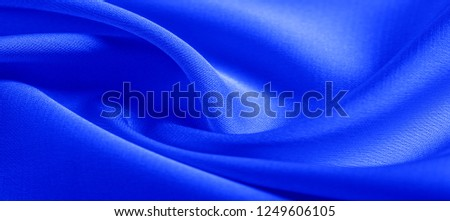 background texture, pattern. blue silk fabric. This lightweight fabric has a brilliant shine that perfectly reflects the light and crumpled texture that adds interest and depth to any fabric design. #1249606105