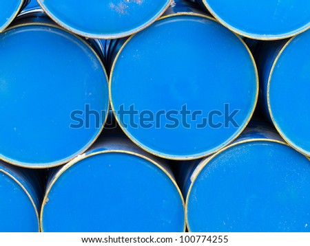 Background texture pattern of stacked blue metal petroleum drums.