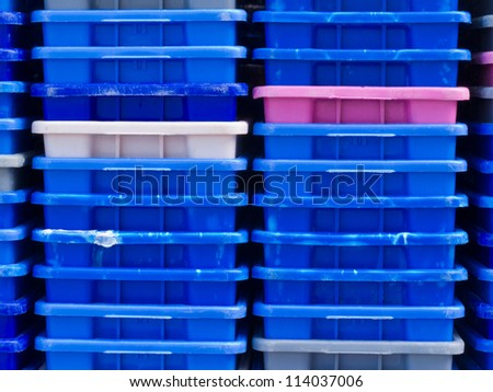 Background texture pattern of stacks of empty colorful plastic containers as used in fishery, wholesale, storage of fresh produce, cargo and retail transportation