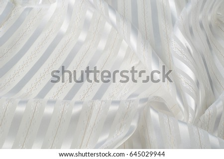 Background texture, pattern. White silk fabric, with a light strip. Closeup of rippled white silk fabric. Smooth elegant golden silk can use as wedding background.  Retro style #645029944