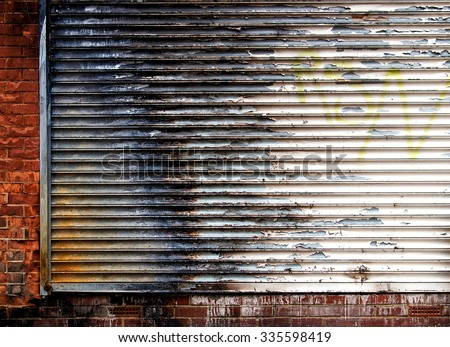Background/ wallpaper -  old store front - metal shutter and brick wall.