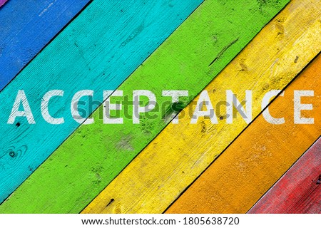 Background with a rainbow-colored LGBT community wooden surface with the words ACCEPTANCE. Concept - acceptance and agreement with LGBT people ストックフォト ©