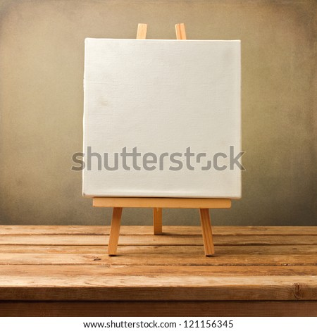 Background with blank canvas on wooden table over grunge background
