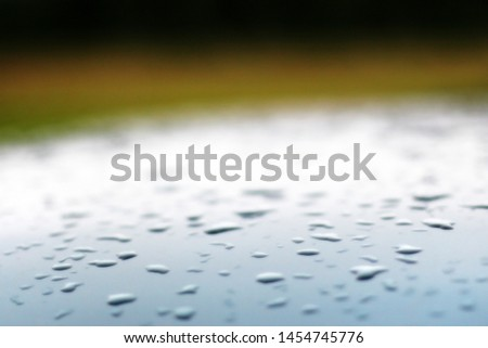 Background with blurred drops on the roof of a silver blue car and a green backdrop. Slight gradient above the roof. There is a place for text. 