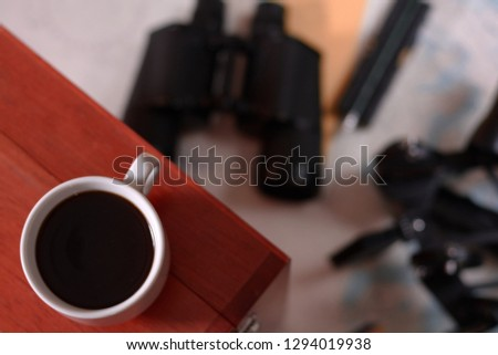 Background with cup of coffee and blurred binocular, pencil, marine sextant lying down on navigational chart. #1294019938