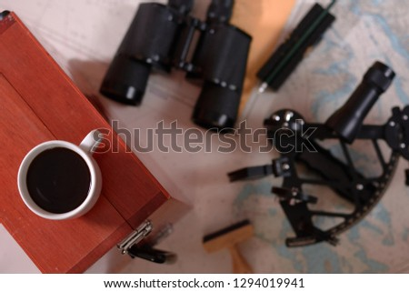 Background with cup of coffee and blurred binocular, pencil, marine sextant lying down on navigational chart. #1294019941