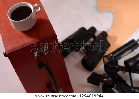 Background with cup of coffee and blurred binocular, pencil, marine sextant lying down on navigational chart. #1294019944