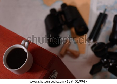 Background with cup of coffee and blurred binocular, pencil, marine sextant lying down on navigational chart. #1294019947