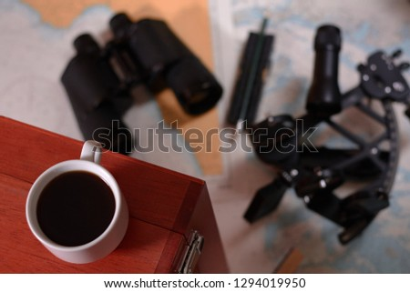 Background with cup of coffee and blurred binocular, pencil, marine sextant lying down on navigational chart. #1294019950