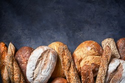 Background with Different Types of Bread on dark surface. Close up. Empty space for text. Bakery concept.